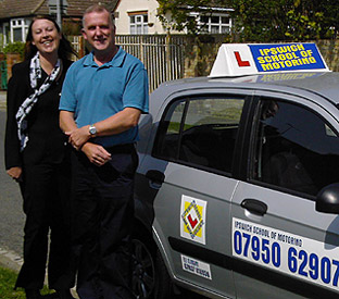 Driving instructors Ele and Richard by an Ipswich School of Motoring car